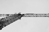 A crane photographed close against a dull grey sky. Black and white photography
