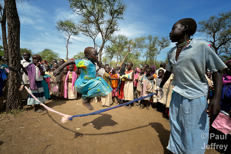 """Children skip rope in a """"Child Friendly Space"""" in the Yusuf Batil refugee camp in South Sudan's Upper Nile State. More than 110,000 refugees were living in four camps in Maban County in October 2012, but officials expected more would arrive once the rainy season ended and people could cross rivers that block the routes from Sudan's Blue Nile area, where Sudanese military has been bombing civilian populations as part of its response to a local insurgency. Conditions in the camps are often grim, with outbreaks of diseases such as Hepatitis E."""
