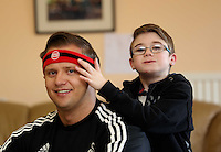 Pictured: 10 year old James Morris (R) helps Swansea City FC ambassador Lee Trundle (L) to put on his red Comic Relief headband. Monday 17 March 2014<br />
