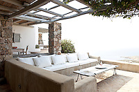A contemporary concrete banquette with white upholstered seats creates a comfortable seating area on one of the terraces overlooking the Mediterranean