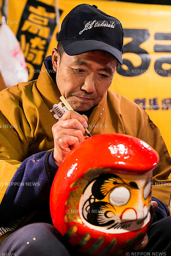 A merchant paints a Daruma doll outside the Shorinzan Daruma Temple in Takasaki City, Gunma Prefecture on January 6, 2016, Japan. Every year thousands of people visit the country's most famous Daruma market (Daruma ichi) held at the Shorinzan Daruma Temple on January 6 and 7. Takasaki City, is known as the capital of Daruma dolls and about 80% of Japan's Daruma are produced there. According to the tradition, Daruma dolls are sold without pupils painted on their eyes. People color in one pupil when a wish is made or a goal set, and when the wish comes true or the goal is achieved they fill in the other pupil. At the end of the year, used Daruma dolls are returned to the temple to be burned. (Photo by Rodrigo Reyes Marin/AFLO)