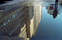 A building a and a silhouette reflected on a watery street