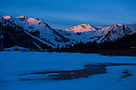 First light at Squaw Valley ski resort with snow covered creek in the foreground near Lake Tahoe, California.