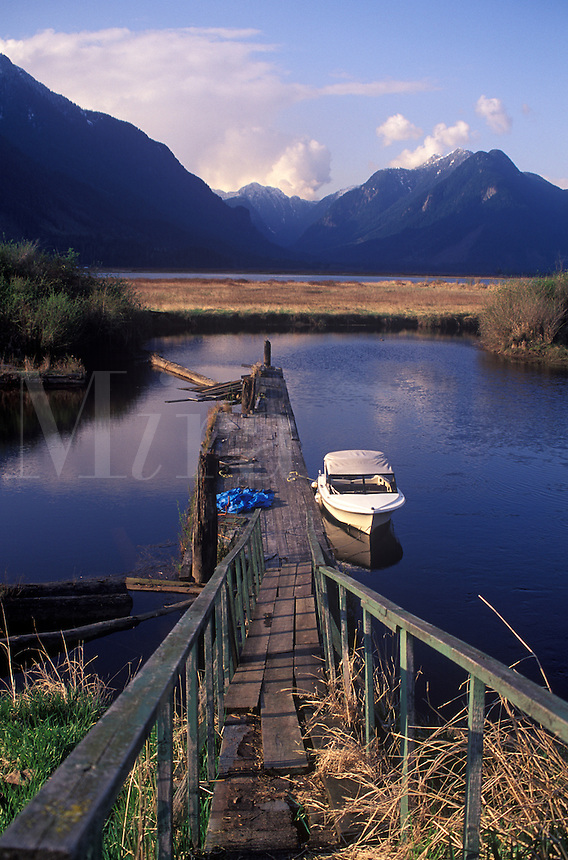 Weathered dock leading to boat on the Pitt River, Majestic Coast Mountain, BC, Canada