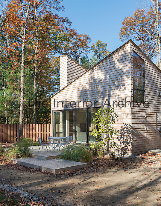 The exterior of a modern cedar wood cottage in New England woods, USA