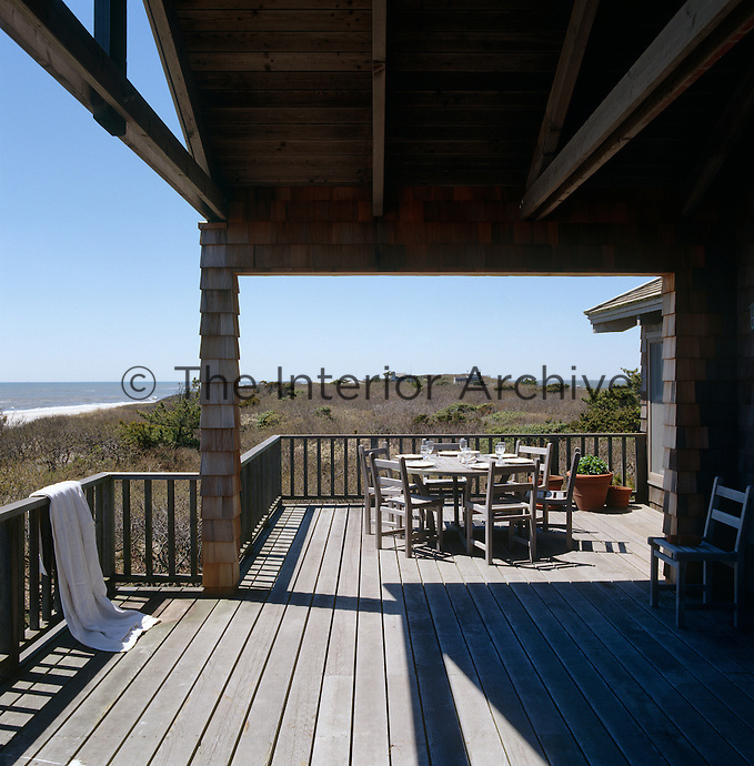 An 'al fresco' dining area on this weathered porch with a view overlooking the dunes and the sea