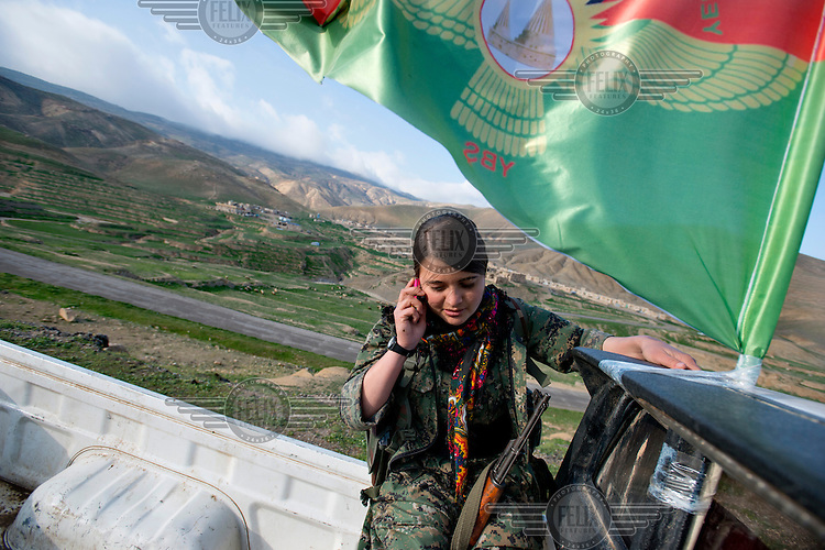Dersim, a 21 year old Yazidi refugee from Sinjar talks to her family on the phone while she sits in the back of a pickup truck. Dersim, who once wanted to become a beautician, is now a member of YBJ, a female Yazidi battalion of the Sinjar Resistance forces (YPG) which is trained by Kurdistan Worker's Party (PKK) fighters from Turkey, Syria and Iran. 'One month after I started working at a local beauty parlour in Sinjar, Islamic State (IS) attacked us. I was running to the mountain and was hoping that Peshmerga and Kurdish fighters would protect us but they ran away too and it was only PKK fighters who protected and supported us. When I saw women from Syria who were fighting for us in August (2014) I thought I also wanted to be like them and protect ourselves in future. I don't want to get married, I don't need children and I'm even ready to die for Sinjar.' Dersim says. <br /> Thousands of Yazidis fled to the mountains when Islamic State (IS) fighters attacked towns and villages around Sinjar in August 2014. Since then Yazidi refugees have been living in precarious conditions with no electricity or running water and children haven't been attending school. Support from the international community has been insufficient and people are dying of hunger and disease. Until December 2014 the mountains were surrounded by IS. Now the southern part of the mountains is still under IS control.