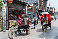 Yangzhou, Jiangsu, China.  Two Pedicabs in Dong Guan Street.