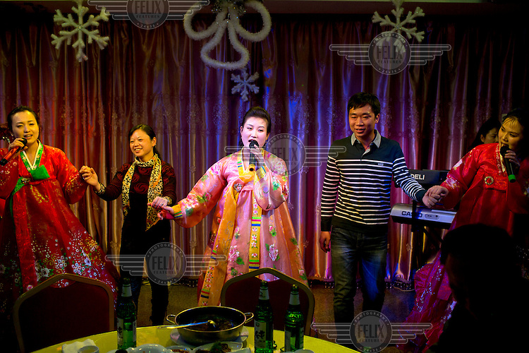 Performers sing and play music with Chinese guests from the audience in a North Korean restaurant. /Felix Features