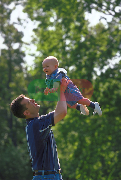 father playing with infant outdoors