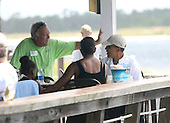 United States President Barack Obama eats lunch at Lime's Bayside Bar and Grill with First Lady Michelle and daughter Sasha while talking to Mike Gorton, owner of 8 Point Water Sports, at Panama City Beach, Florida USA on Saturday, 14 August  2010.  The First Family is visiting the area to help promote tourism and check up on clean up efforts from the aftermath of the Deepwater Horizon Oil spill. .Credit: Dan Anderson / Pool via CNP