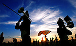 A pair of Johnston marching band trombonists play under a setting sun while rehearsing with bandmates before  the Johnston - Ottumwa football game September 16, 2005.