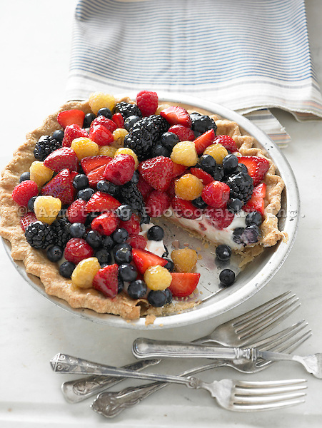 Berry pie with strawberries, blueberries, red raspberries, golden raspberries, and blackberries on a sweet sour cream filling.