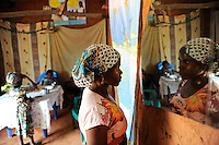 ANGOLA Kwanza Sul, rural development project ACM-KS, woman in her clay hut looking into mirror in village Cassombo / ANGOLA Kwanza Sul, laendliches Entwicklungsprojekt ACM-KS, Dorf Cassombo, Frau Felismina Napitango 43 Jahre zu Hause, schaut in den Spiegel