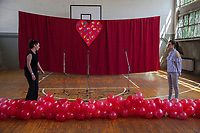 Serbia. Zitkovac is a village in Central Serbia situated in the municipality of Aleksinac, in the Nišava District. « Vuk Karadzic » Elementary School. School gym indoor. A teacher and a student are finishing event's preparation. Red inflated balloons and three microphones on stand. Red curtain and heart with colorful painted hands prints. 19.4.2018 © 2018 Didier Ruef