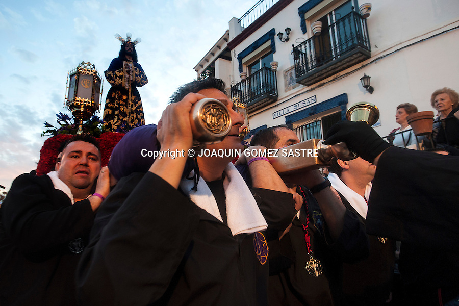 The procession of  the holy  cross runs through the narrow streets of the same name in Alicante