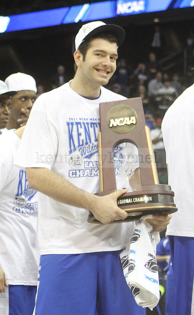 Josh Harrellson holds up the region trophy after defeating UNC in the Elite 8 game of the 2011 NCAA Basketball Tournament, at the Prudential Center, in Newark, NJ.  Photo by Latara Appleby | Staff