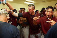 Mahoning Valley Scrappers Nolan Jones douses manager Luke Carlin (left) as they celebrate in the locker room after winning the division title during the second game of a doubleheader against the Batavia Muckdogs on September 4, 2017 at Dwyer Stadium in Batavia, New York.  Mahoning Valley defeated Batavia 6-2 to clinch the Pinckney Division Title.  (Mike Janes/Four Seam Images)