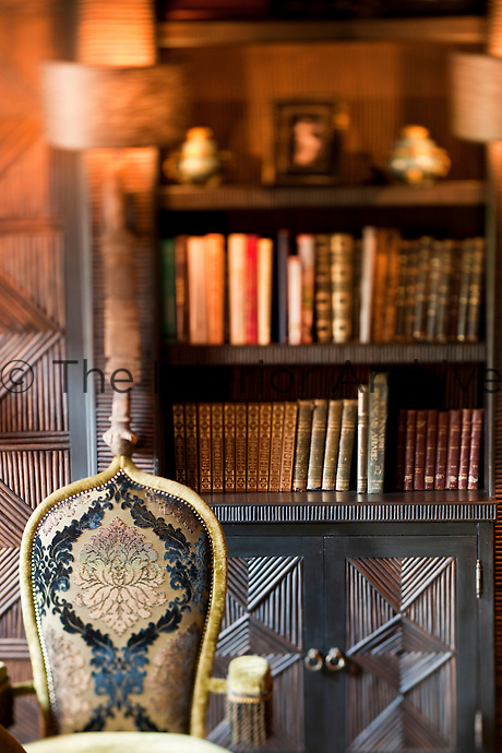In the library furnished with tasteful pieces, a decorative Berber technique covers the wall and the cabinet