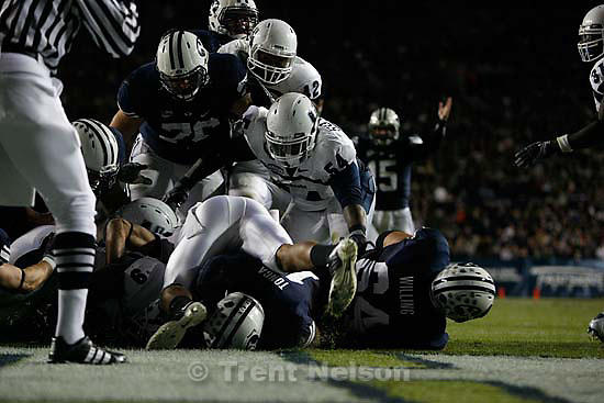 BYU running back Manase Tonga (bottom of the pile) dives into the end zone as quarterback Max Hall (rear left) signals the touchdown. The scoring run gave BYU a 21-7 first half lead. BYU vs. Utah State University college football Friday, October 2 2009 in Provo.