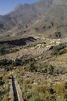 Wadi Bani Kharus, Oman.  Irrigation Calan (Falaj) Carries water down Mountainside to Village and date Palms below.