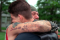 Men age 55 and 24 embracing at Vietnam wall on Memorial Day. St Paul Minnesota USA