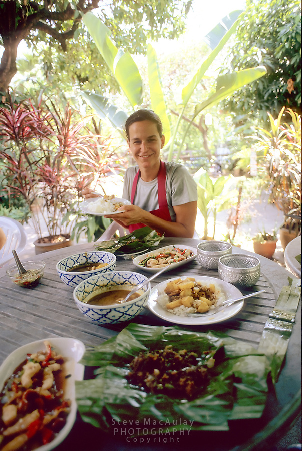 Female traveler enjoying the Thai food she just preapred at Thai cooking class, Chiang Mai, Thailand