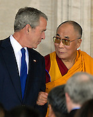 Washington, DC - October 17, 2007 -- The 14th Dalai Lama, Tenzin Gyatso, is helped from the stage by United States President George W. Bush at The Capitol where he accepted the Congressional Gold Medal, the nation's highest and most distinguished civilian award in Washington, D.C. on Wednesday, October 17, 2007..Credit: Ron Sachs/CNP