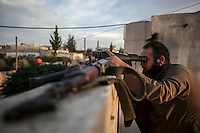 In this Thursday, Sep. 19, 2013 photo, a Syrian opposition fighter watchs over as heavy fighting sparks out in the neighbouring village of Kafr Nabuda in the Idlib province countryside, Syria. (Photo/AP).