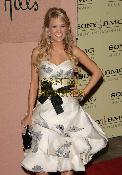 CARRIE UNDERWOOD.attends The Sony / BMG Post Grammy Party held at The Beverly Hills Hotel in Beverly Hills, California, USA, February 11 2007..half length strapless white dress black sash belt bow shoes hand on hip .CAP/DVS.©Debbie VanStory/Capital Pictures