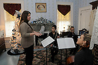 STAFF PHOTO FLIP PUTTHOFF <br /> PEEL MANSION CHRISTMAS<br /> Katie Priest, left, gets students with the Northwest Arkansas Classical Academy String Quartet ready to play a holiday tune on Saturday Dec. 20 2014 during the Christmas open house at The Peel Mansion and Heritage Gardens in Bentonville. Visitors toured rooms of the historic home that were decorated in various themes while docents in period clothiung revealed the mansion's history. The open house was the last opportunity for visitors to see the Peel Manstion decorated for Christmas. Student musicians are Camille Wagner from left, Laruen Rabal and Marianna Ernst. Shreya Gangaram, not shown, also played with the quartet.
