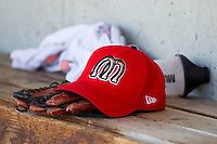 A Billings Mustangs cap sits on a glove in the dugout prior to the game against the Orem Owlz at Brent Brown Ballpark on July 22, 2012 in Orem, Utah.  The Mustangs defeated the Owlz 13-8.  (Brian Westerholt/Four Seam Images)