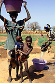 Tankular, The Gambia. Smiling woman with bucket of water for crop irrigation and smiling girl and baby.