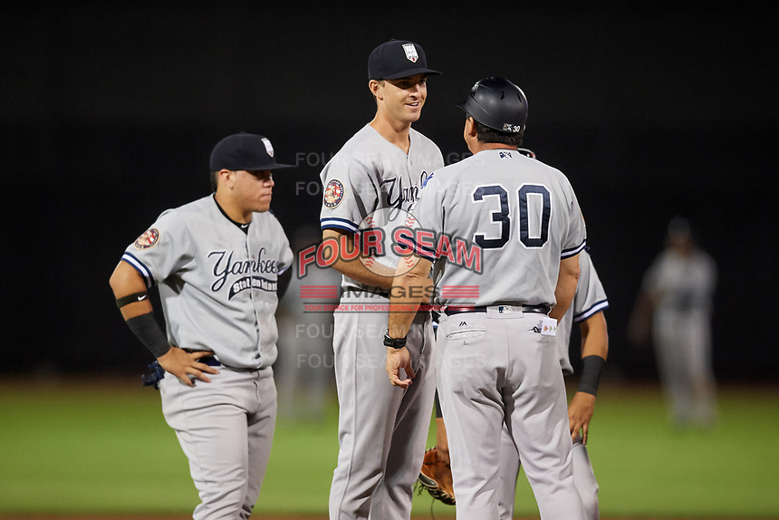 Staten Island Yankees relief pitcher Aaron McGarity (14) is greeted by manager Lino Diaz (30) on the mound after entering the game on a pitching change as third baseman Andres Chaparro (26) looks on during a game against the Aberdeen IronBirds on August 23, 2018 at Leidos Field at Ripken Stadium in Aberdeen, Maryland.  Aberdeen defeated Staten Island 6-2.  (Mike Janes/Four Seam Images)