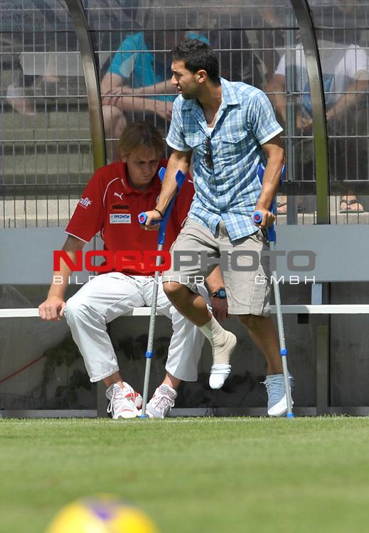 Emre OEZTUERK ( #20 Sandhausen ), der sich im Training verletzt hat,  mit bandagiertem Fuss und Kruecken, dahinter Trainer Gerd DAIS ( Sandhausen ) auf der Bank                                                                                            Foto © nph (  nordphoto  )