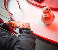 "A visitor controls a Star Wars droid toy in the Target ""Wonderland!"" pop-up store in the Meatpacking District in New York on its grand opening day, Wednesday, December 9, 2015. According to Target the store combines physical and digital shopping using medallions given to visitors with an embedded RFID chip. Tapping the chip to an antenna near the product lets you order it. The store is an experiment in technology replacing shopping carts with chips.  (© Richard B. Levine)"