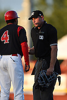 Umpire Christopher Stump listens to manager Angel Espada (4) during a game between the Williamsport Crosscutters and Batavia Muckdogs on August 25, 2014 at Dwyer Stadium in Batavia, New York.  Williamsport defeated Batavia 3-0.  (Mike Janes/Four Seam Images)