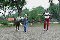 Shetland-Pony, Shetlandpony, Shetty, Shetti, Ponyhof, Shetland - Pony wird eingeritten, zunächst Führung an der Longe durch Reitlehrerin und am Halfter durch Mädchen, Reiten