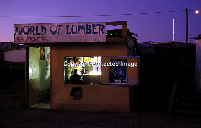 dippocc00046.People. Occupation. A barber is working late in his shop close to Nonqubela train station on November 4, 2003 in Site C Khayelitsha township outside Khayelitsha, South Africa. 'World of Lumber' is the name of the barber. Lifestyle, poverty. .©Per-Anders Pettersson/ iAfrika Photos