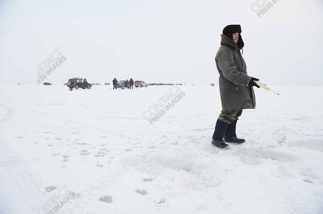 Men drove out onto the frozen sea off Magadan to fish on a Sunday morning. Russia, February 5, 2011