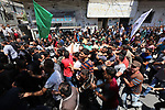 Mourners carry the body of Palestinian Mohammed Abu Namous, one of three armed Palestinians killed overnight in Israeli fire along the border with the Gaza Strip, during his funeral in Beit Lahya in northern Gaza strip on August 18, 2019. Israeli forces last night killed three Palestinians and injured a fourth one in an artillery attack near the town of Beit Lahia, north of the Gaza Strip, according to the Ministry of Health. Photo by Ramadan al-Agha