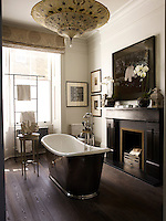 A tub with Lefroy Brooks fittings in the master bathroom stands in front of a fireplace original to the property