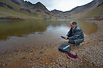 Freddy Llanos, a professor of mining engineering at Tomas Frias University, samples water quality in a lake below the Kumurana Mine near Caiza D, Bolivia. The mine, which is closed, produces highly toxic acid runoff that negatively impacts the farms and lives of people living downstream. Llanos is working with an international coalition that is working with local miners and farmers to clean up the mine's runoff.