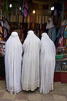 Women in burkas shopping.