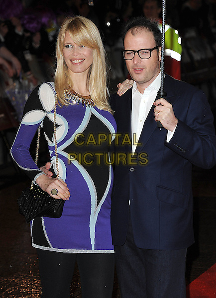"CLAUDIA SCHIFFER & MATTHEW VAUGHN.Attending The European Premiere of ""Kick-Ass"", Empire Leicester Square, London, England, UK, .22nd March 2010..arrivals half length black suit white shirt purple white print dress patterned pattern chain strap gold bag pregnant maternity married couple husband wife  smiling umbrella holding raining glasses vaughan navy blue .CAP/BEL.©Tom Belcher/Capital Pictures."