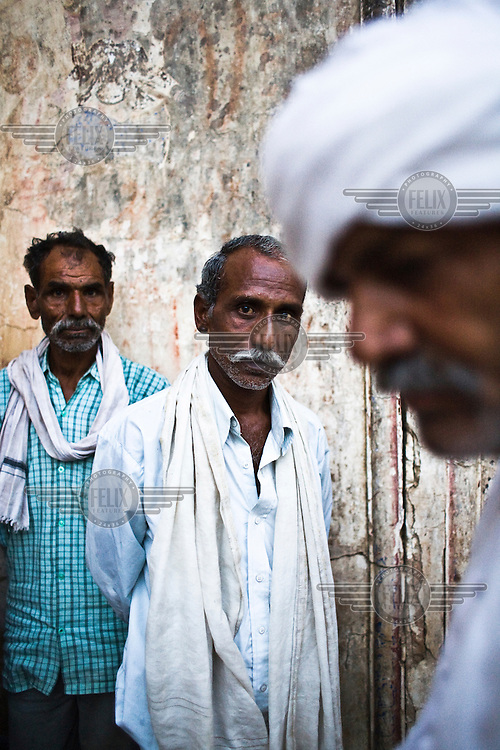 Gajendra (centre) and Surinder Singh (right), both former dreadlocked dacoits (bandits), outside the temple in Hanumangarhi village.