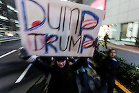 "A woman holds a sign saying ""Dump Trump"" during a protest march by members of the Democratic Party Abroad organisation to mark the inauguration of President Donald Trump, Tokyo, Japan. Friday January 20th 2017 Around 400 people took apart in the march, which started in Hibiya Park at 6:30pm and finished in Roppongi just before 8pm, to honour the service given by President Obama and to protest against the illiberal policies expected of the new administration of President  Trump."