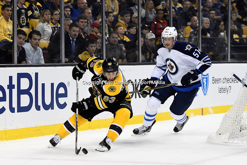 Thursday, October 8, 2015: Boston Bruins left wing Brad Marchand (63) works the puck through the corner with Winnipeg Jets defenseman Tyler Myers (57) closing in during the NHL game between the Winnipeg Jets and the Boston Bruins held at TD Garden, in Boston, Massachusetts. Winnipeg defeated Boston 602 in regulation time. Eric Canha/CSM