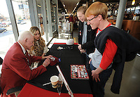"NWA Media/ANDY SHUPE - Michael York, a sophomore at the University of Arkansas from Fayetteville, right, and junior Alexis Lee of Delight, watch as Frank Broyles, former coach and director of athletics at the university, left, signs a hat and a copy of the book, ""An Arkansas Legend: The Life & Legacy of Frank Broyles,"" Friday, Dec. 12, 2014,  during a book signing at the University Bookstore on the University of Arkansas campus in Fayetteville. Seated with Broyles is his granddaughter, Molly Arnold Gay. Ten percent of the proceeds from sales of the boo, which was published by NWA Media and the Arkansas Democrat-Gazette, will be donated to the Frank and Barbara Broyles Foundation: Care Givers United for Alzheimer's and Dementia. Broyes, 89, will take part in another event to sign limited-edition footballs celebrating the 50th anniversary of the 1964 National Championship season Wednesday at 2:30 p.m. at the Bank of Fayetteville with all proceeds benefitting the foundation."