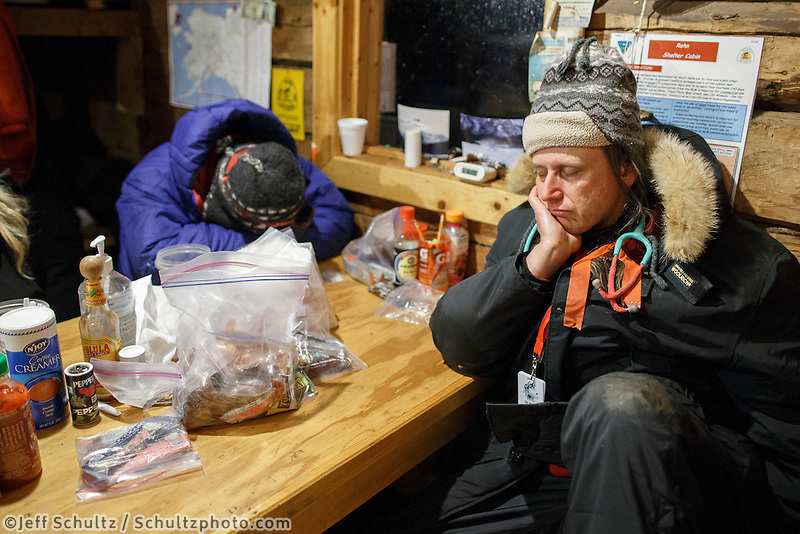 Rohn Volunteers, up all night with teams, sleep at the table in the early morning on Tuesday March 4 during Iditarod 2014 . PHOTO BY JEFF SCHULTZ/IDITARODPHOTOS.COM  USE ONLY WITH PERMISSION